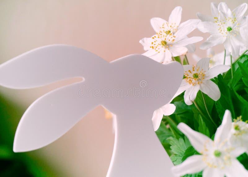 Påskkaninen med fjädrar blommor royaltyfri foto
