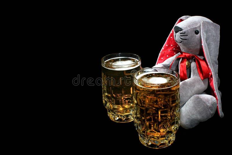 Påskkaninen med två rånar av öl mot svart bakgrund arkivbild