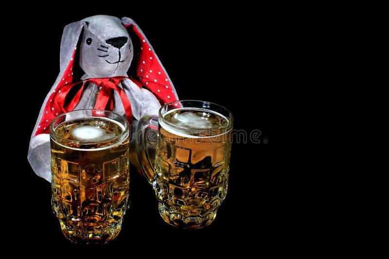 Påskkaninen med två rånar av öl mot svart bakgrund royaltyfria foton