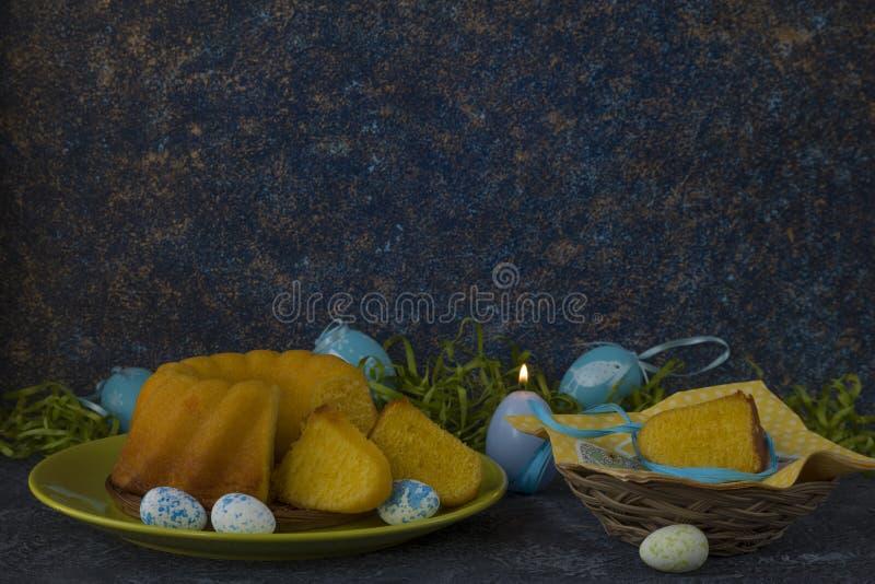 Påskkorgen med färgade påskägg på mörker stenar tabellen arkivfoton