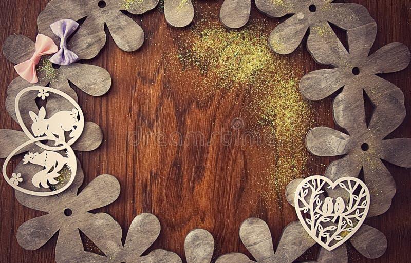 Påskkort, på en bakgrund av naturligt trä med pilbågar, blommor och påskgarneringar royaltyfria foton