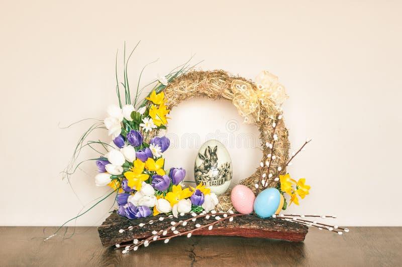 Påskkrans som göras av hö med konstgjorda blommor och ägg royaltyfri bild