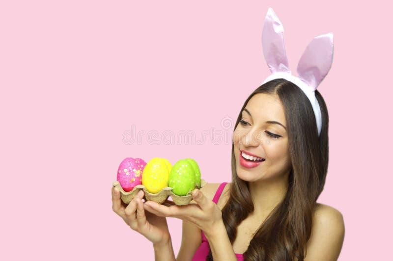 Påskkvinnabegrepp Den gulliga flickan med kaninen gå i ax att se till hennes ägglåda av färgrika påskägg som isoleras på rosa bak arkivbilder