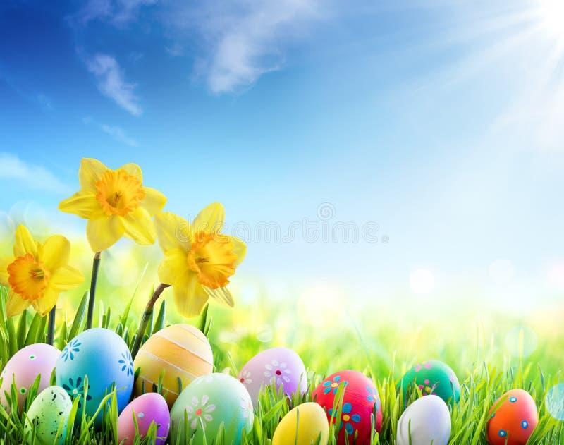 Påskliljor och färgrika dekorerade ägg på Sunny Meadow - påsk royaltyfri fotografi