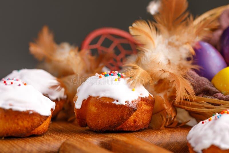 Påskmuffin och ägg som målades i ovanliga färger, dekorerade med fjädrar royaltyfri foto