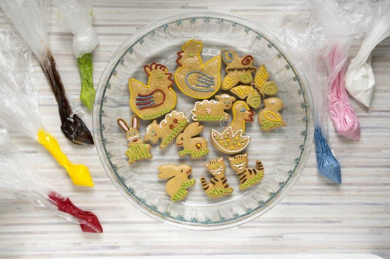 Påskpepparkakor i bakningbunke, färgläggningmaterial som göras från ägget, och sockervit i plastpåsar, gräsplan, brunt, guling so royaltyfri foto