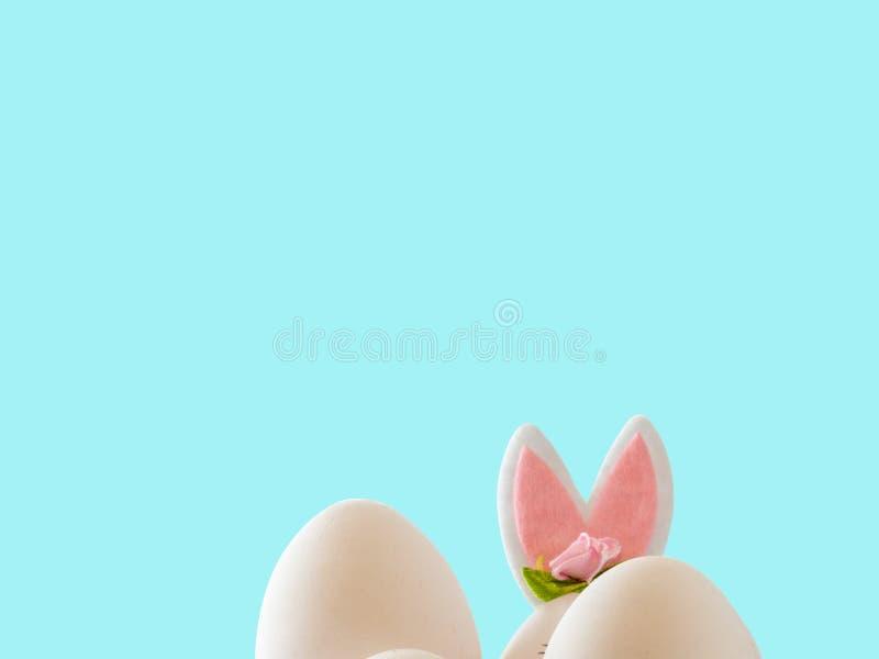 Påskplats med kulöra ägg, easter kanin, blå bakgrund arkivbild
