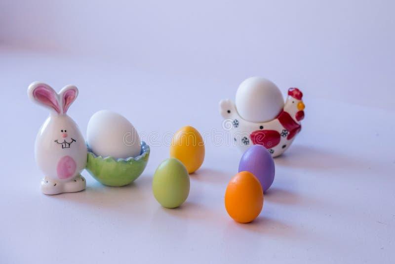 Påsksammansättning: ägg och porslinstatyetter royaltyfria foton