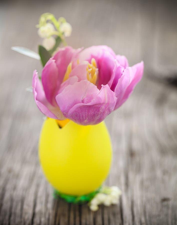 Påsksammansättning med ägg- och pastelltulpanblomman och liljanolla fotografering för bildbyråer