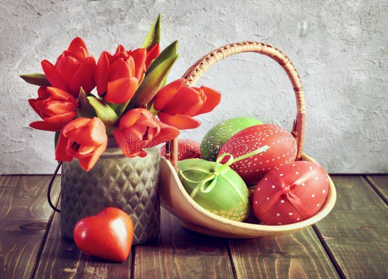 Påskstilleben med röda tulpan, den slågna in gåvan och påskägg arkivbilder
