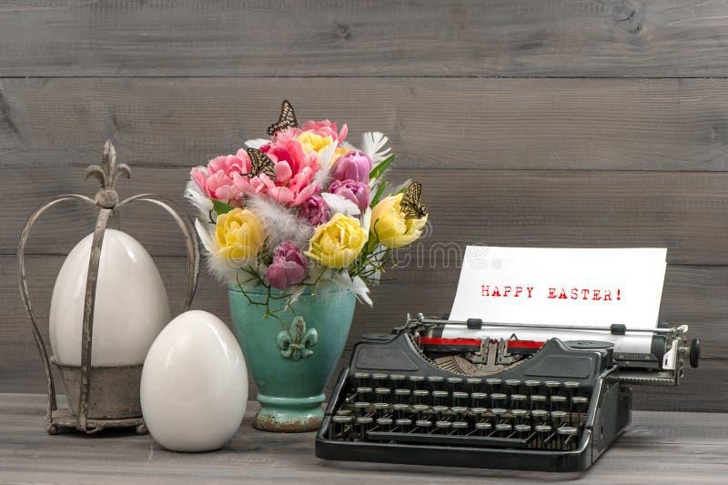 Påskstilleben med tulpan, ägg och skrivmaskinen arkivbilder