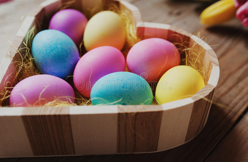 Påsksymbol - kulöra ägg i en formad hjärta bowlar royaltyfria foton