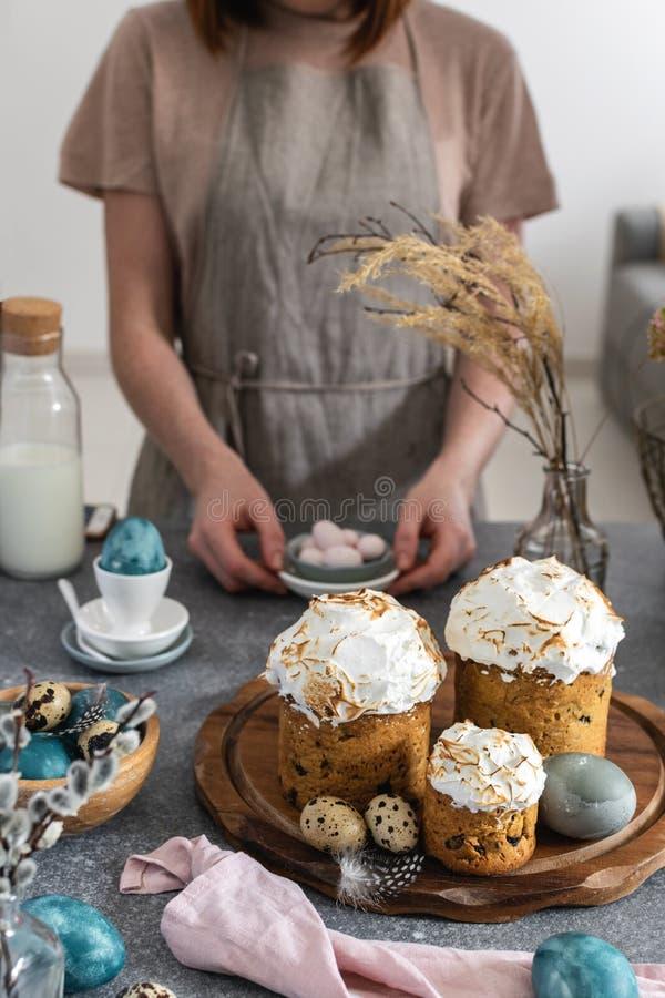 Påsktabell - kvinnliga händer som tjänar som godisar i äggform, den easter kakan, mjölkar flaskan, färgade ägg, vaktelägg royaltyfri foto