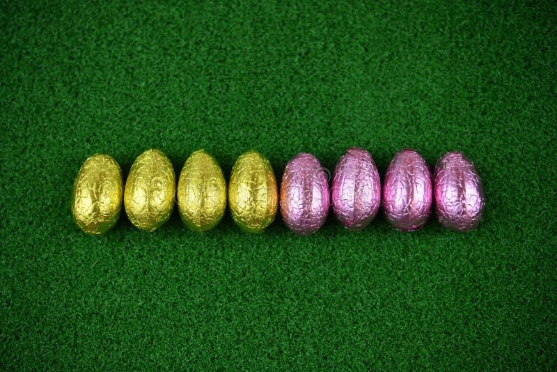 Påsktid med ljusa kulöra skinande slågna in chokladeaster ägg på en vårbakgrund för grönt gräs royaltyfria bilder