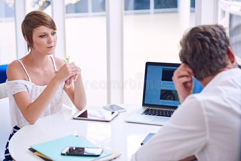Påtaglig motsättning mellan mannen och kvinnlign blir partner med under affärsmöte arkivbild