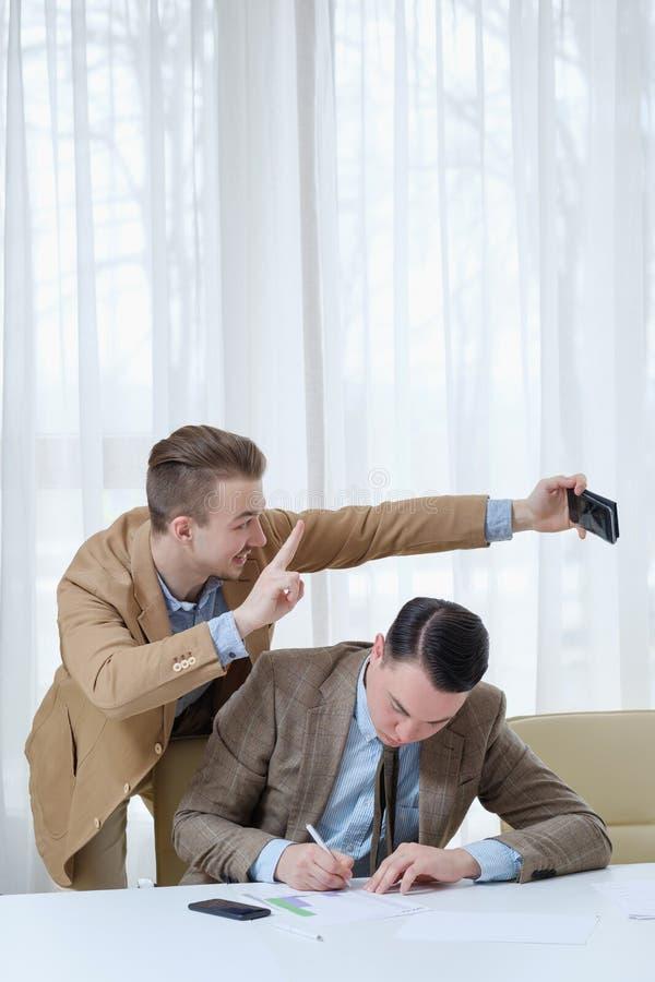 Påträngande etik för kontor för kollegaselfiearbete royaltyfri fotografi
