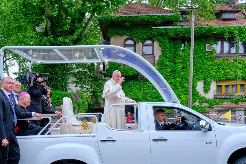 P?ve Francis som vinkar till folket i Bucharest fr?n hans popemobile, n?r att ha l?mnat folkr?ddningdomkyrkan, under bes?k 2019 royaltyfri foto