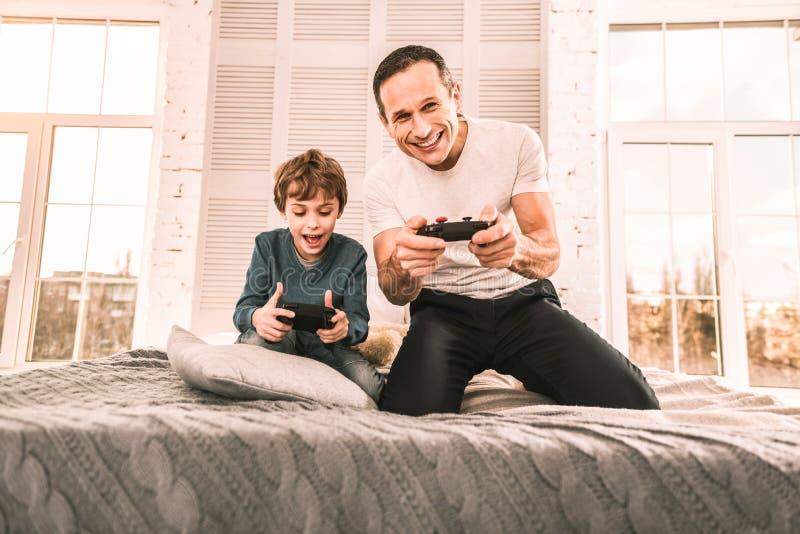 Père étant fier de se pour battre son fils dans un jeu images libres de droits