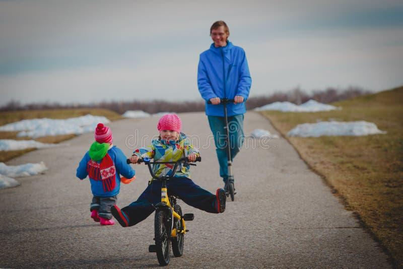 Père actif de famille de spor sur le schooter avec des enfants dehors, peu de fille sur le vélo photographie stock libre de droits