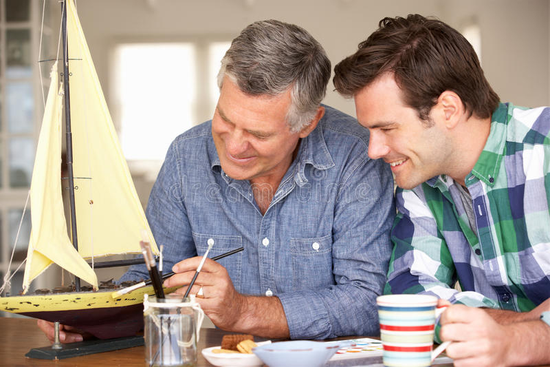 Père adulte et fils modelant un bateau ensemble photos stock