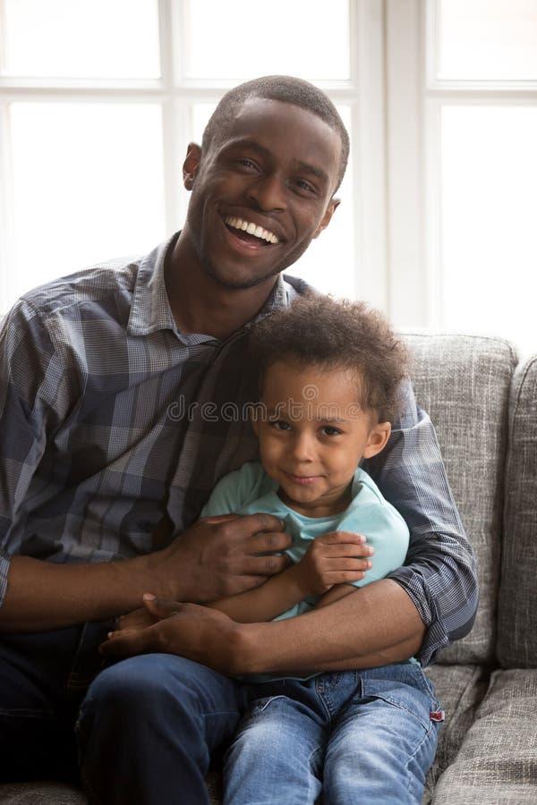 Père affectueux avec le petit fils s'asseyant regardant l'appareil-photo à l'intérieur images stock