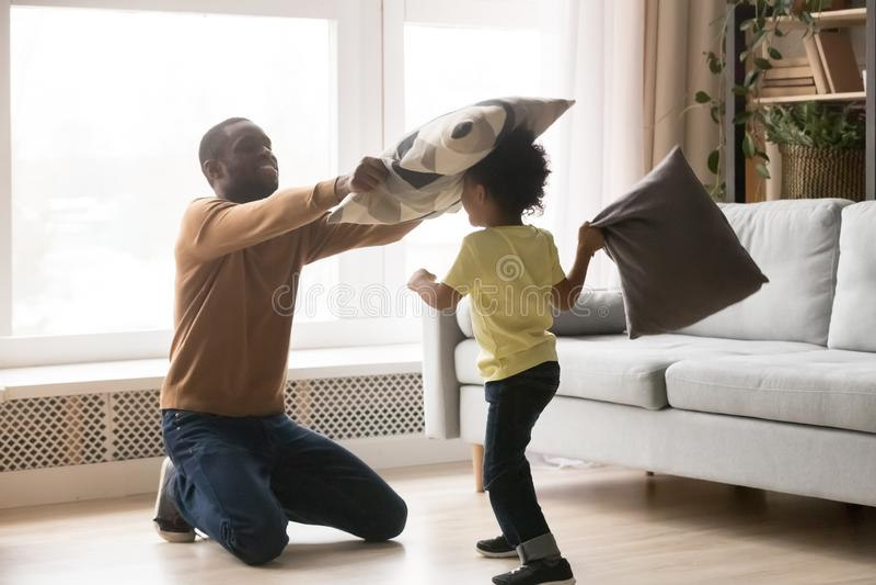 Père africain et petit combat de fils jouant avec des oreillers photo libre de droits