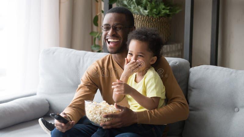 Père africain tenant dessus le film de observation de petite famille de fils de recouvrement image libre de droits