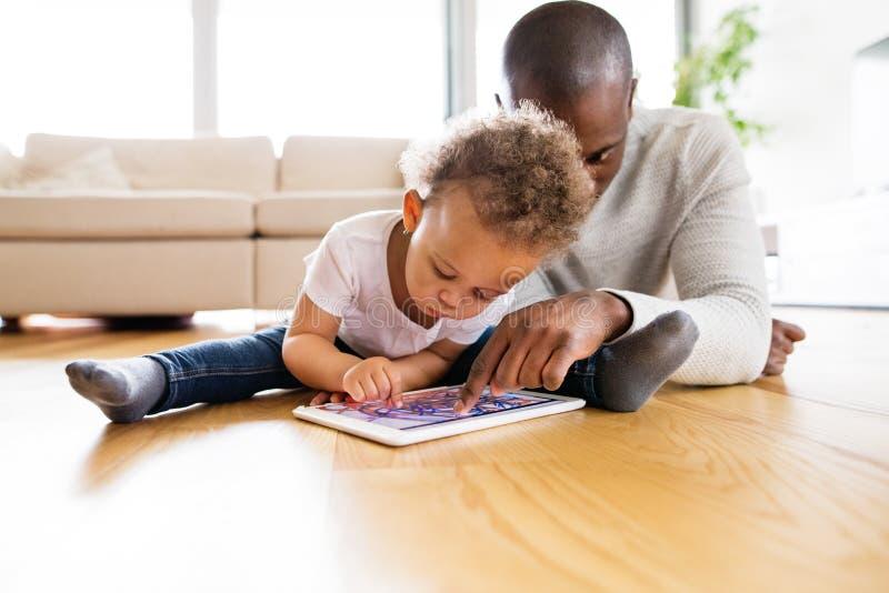 Père afro-américain avec la petite fille avec le comprimé à la maison photo stock