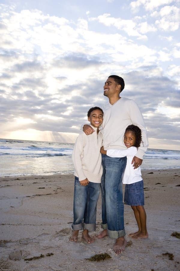 Père afro-américain et deux enfants sur la plage image stock