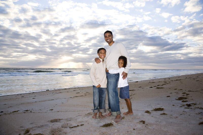 Père afro-américain et deux enfants sur la plage images libres de droits