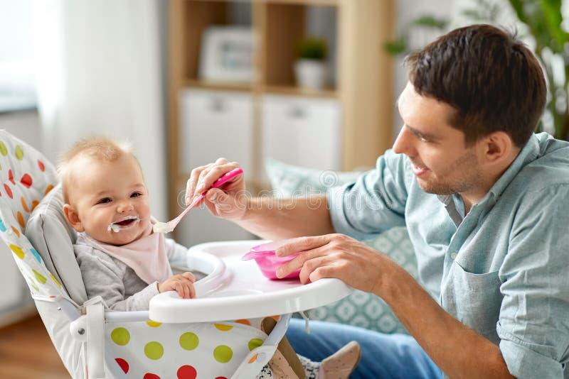 Père alimentant le bébé heureux dans le highchair à la maison photo stock