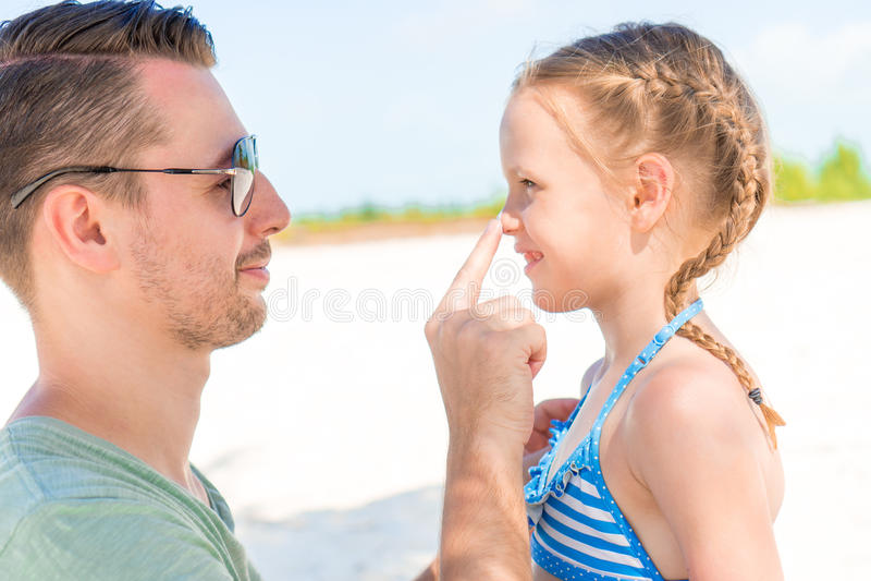 Père appliquant la crème du soleil au nez de fille Portrait de fille mignonne dans le suncream image stock