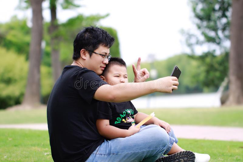 Père asiatique et fils ayant l'amusement dans le stationnement photographie stock