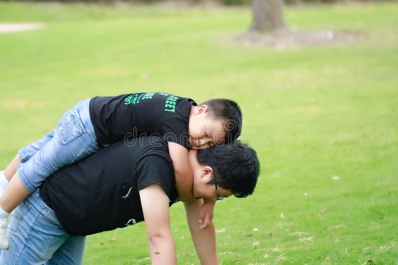 Père asiatique et fils ayant l'amusement dans le stationnement images stock