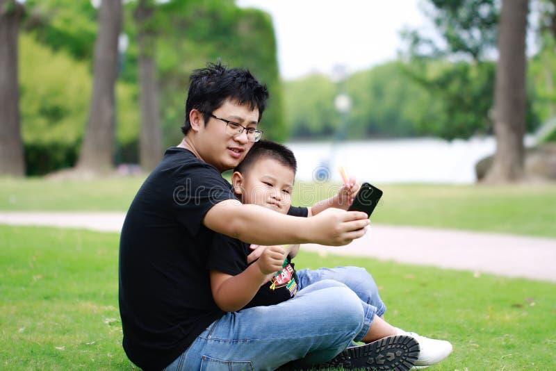 Père asiatique et fils ayant l'amusement dans le stationnement photos libres de droits