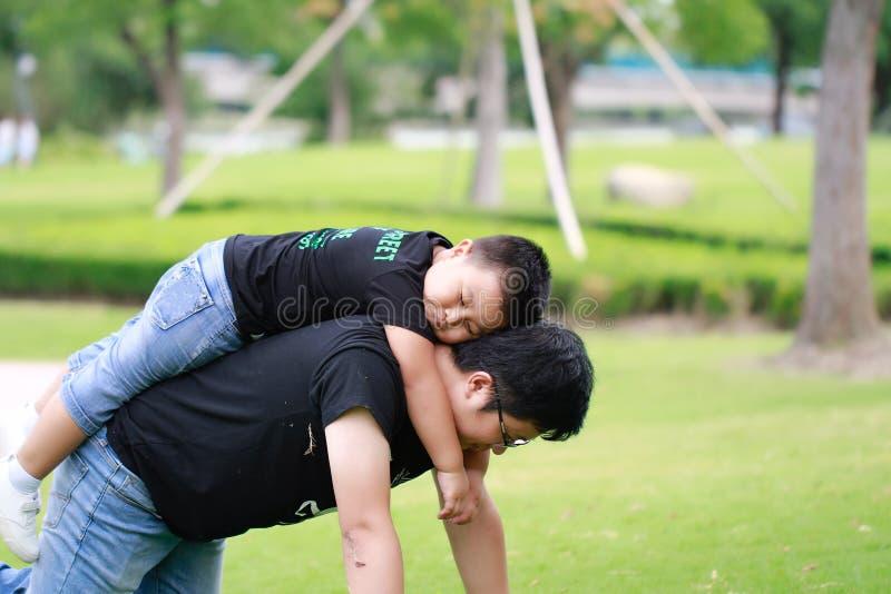 Père asiatique et fils ayant l'amusement dans le stationnement photo libre de droits