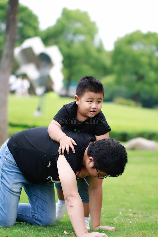 Père asiatique et fils ayant l'amusement dans le stationnement photos stock