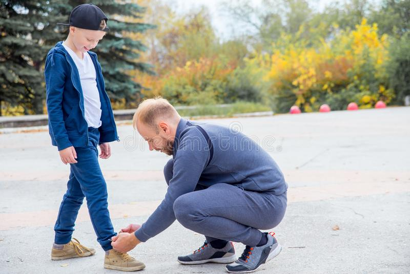 Père attachant la dentelle du fils tout en jouant en parc images stock