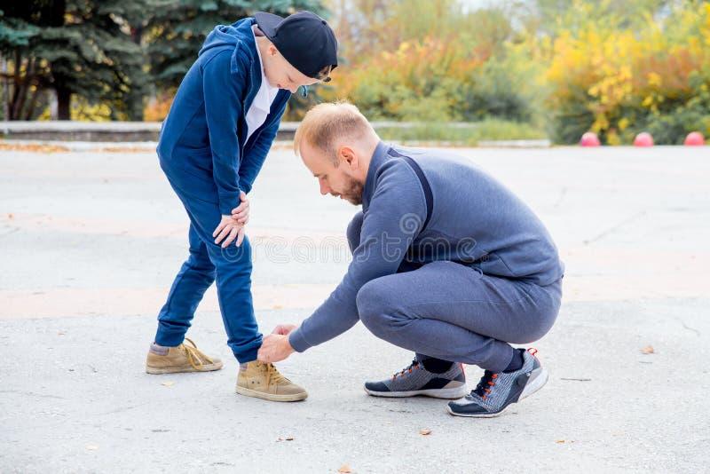 Père attachant la dentelle du fils tout en jouant en parc images libres de droits