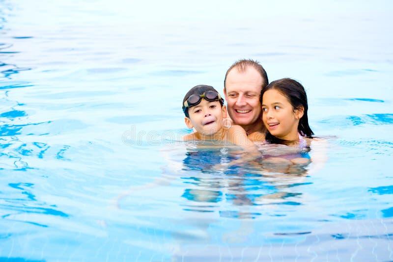 Père avec des enfants appréciant la piscine photo stock