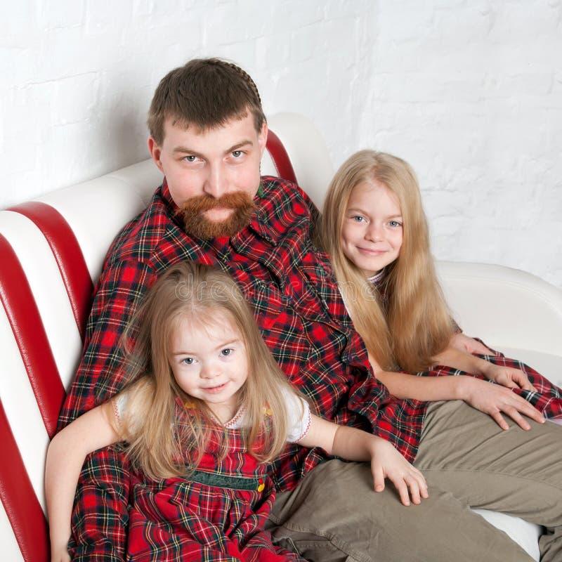 Père avec deux filles caressant images libres de droits