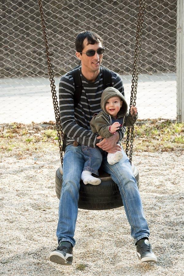 Père avec l'enfant sur l'oscillation photographie stock