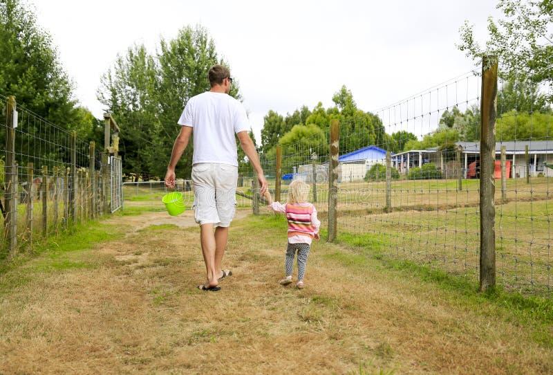 Père avec la fille observant le secteur de terres cultivables Quelque part en Nouvelle Zélande photographie stock libre de droits