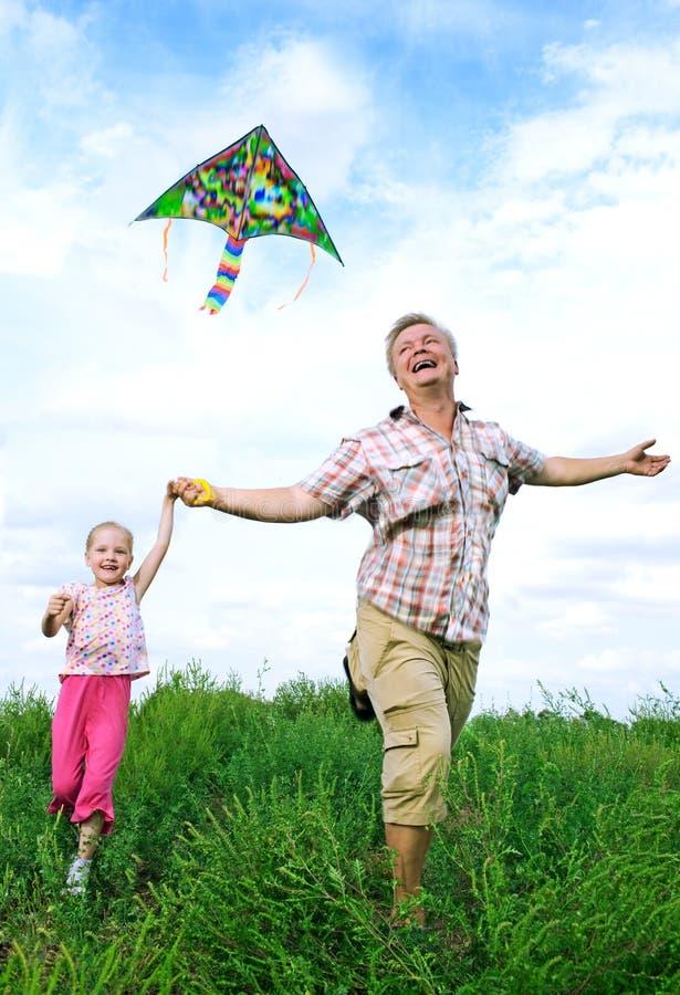 Père avec le descendant jouant avec le cerf-volant photographie stock libre de droits