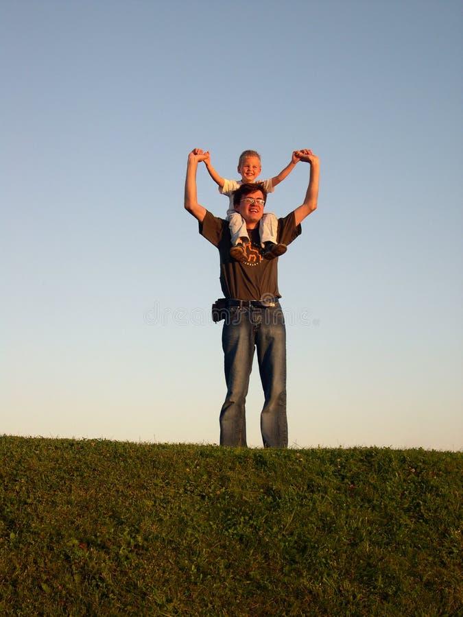 Père avec le fils sur des épaules sur le crépuscule photographie stock libre de droits