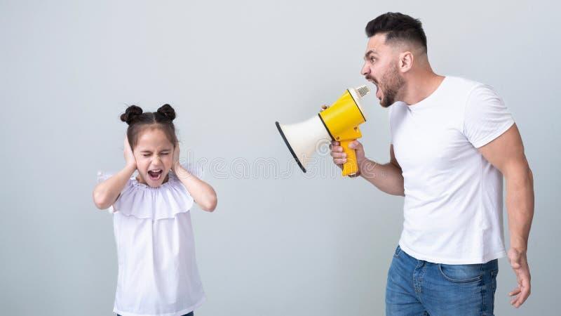 Père avec le mégaphone criant aux oreilles se fermantes de fille photos libres de droits