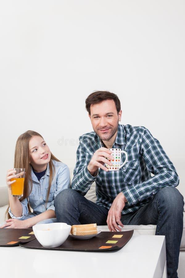 Père avec sa fille prenant un petit déjeuner photographie stock