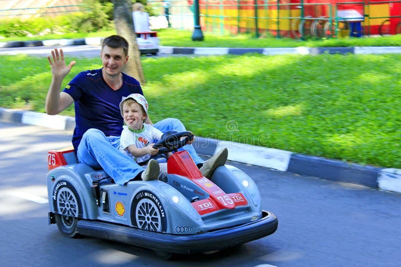 Père avec sa voiture électrique de jouet d'entraînement de fils sur la rue Gens heureux image libre de droits