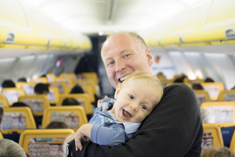 P?re avec ses six mois de b?b? gar?on dans l'avion photos stock
