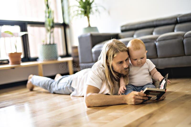 Père avec son bébé et un livre dans le salon photographie stock